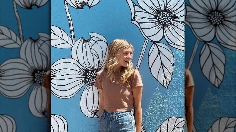 Gabby Petito smiler med blomstermaleri i bakgrunnen