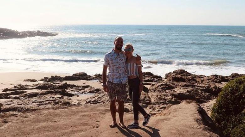 Brian Laundrie og Gabby Petito smiler med vann i bakgrunnen