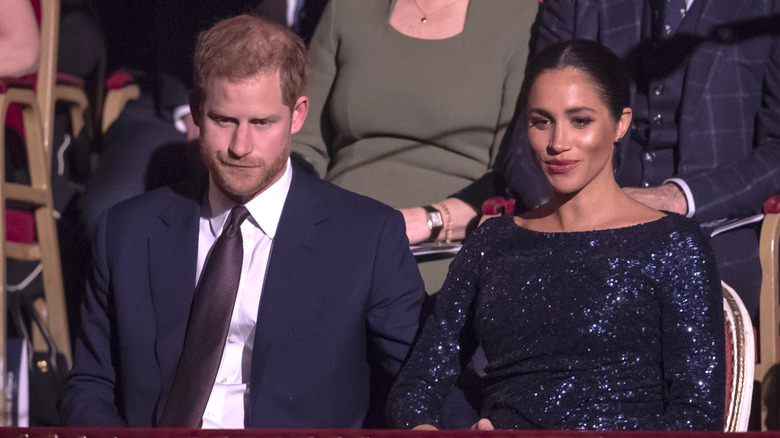 Prins Harry og Meghan Markle ser ned