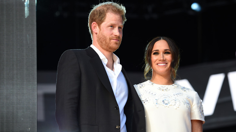 Prins Harry og Meghan Markle smiler på scenen