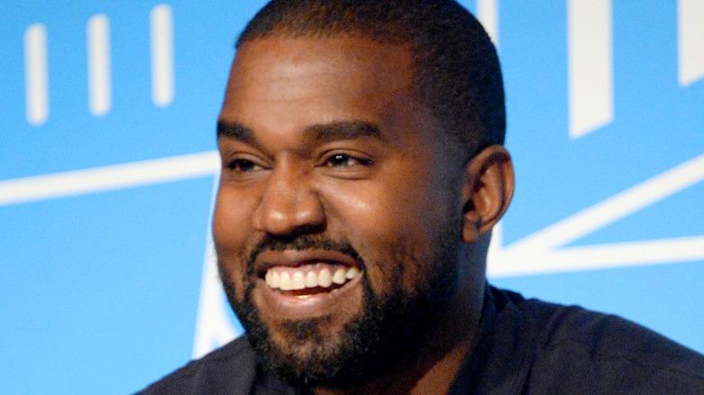 Kanye West smiler og ler