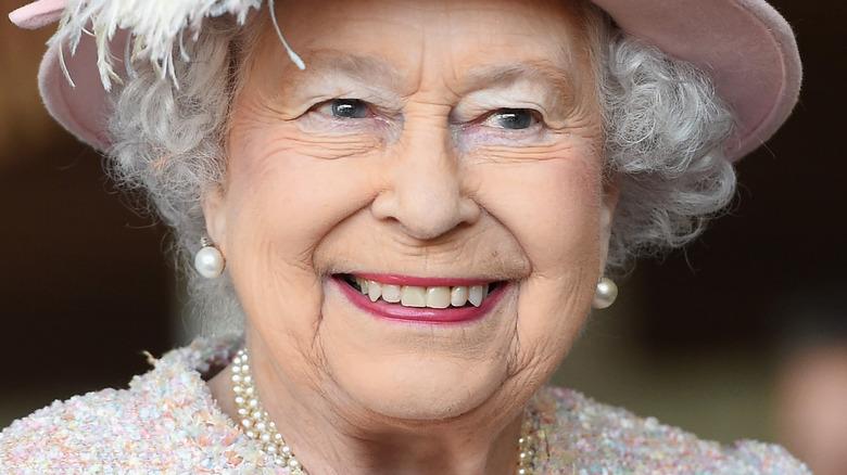 Dronning Elizabeth smiler til et forlovelse