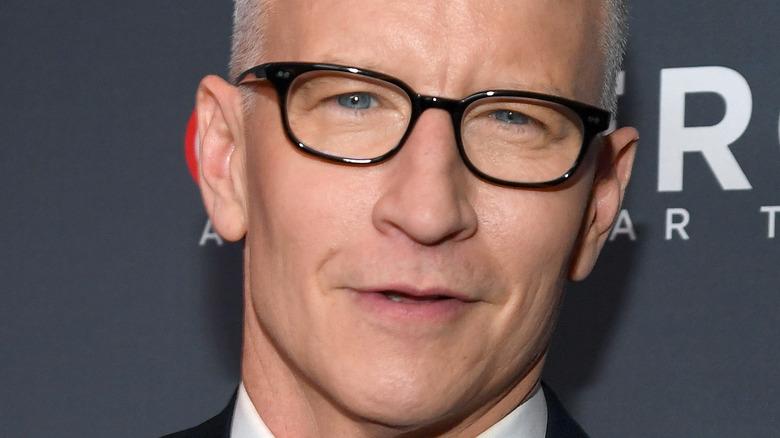 Anderson Cooper smiler med svarte glass.